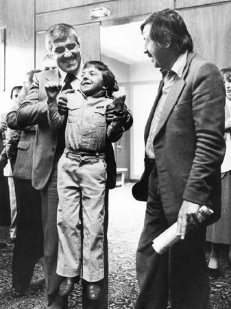 """David Bennent, der 12-jährige Hauptdarsteller, wird auf der Pressekonferenz vor der Uraufführung des Films """"Die Blechtrommel"""" am 03.05.1979 in Berlin von seinem Filmvater Mario Adorf hochgehoben. Rechts der Autor der Romanvorlage,"""