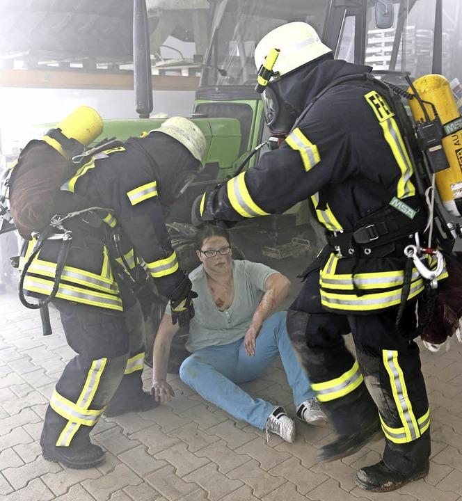 Das Opfer im T-Shirt, die Lebensretter mit Atemschutz im Einsatz    Foto: Bernhard Rein, Bernhard Rein