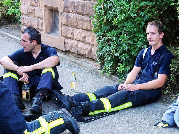 Erschöpfte Feuerwehrmänner nach einem schweißtreibenden Einsatz