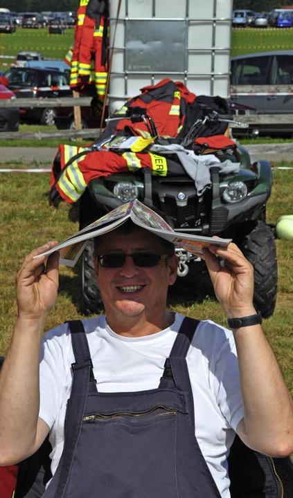 Georg Metzger von der Hüttener Feuerwehr mit seinem improvisierten Sonnenschutz  | Foto: Kirsten Lux