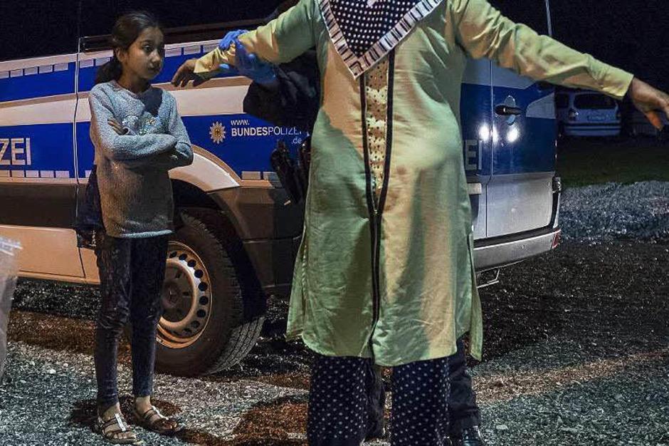 Eine syrische Frau und ihre Tochter werden an der deutsch-österreichischen Grenze kontrolliert. (Foto: AFP)