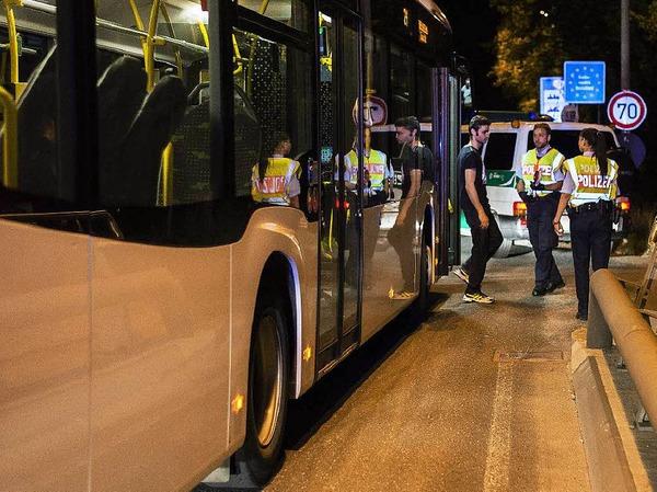 Ein Flüchtling wird in einem Bus kontrolliert.