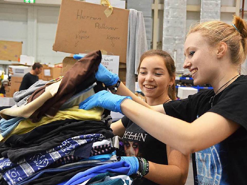 Natascha Held und Nina Orgel (von links) legen Hemden und T-Shirts zusammen.  | Foto: Sina Gesell