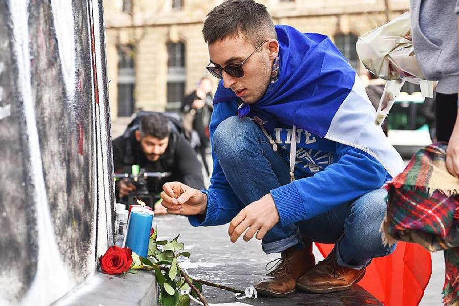 Ein Mann zündet am Place de la Republique in Paris eine Kerze an. (Foto: dpa)