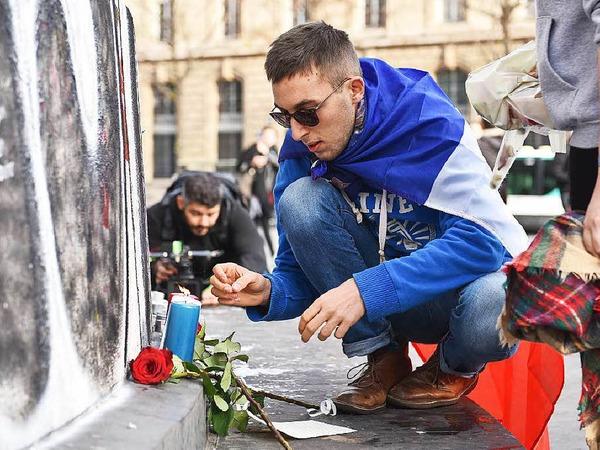 Ein Mann zündet am Place de la Republique in Paris eine Kerze an.