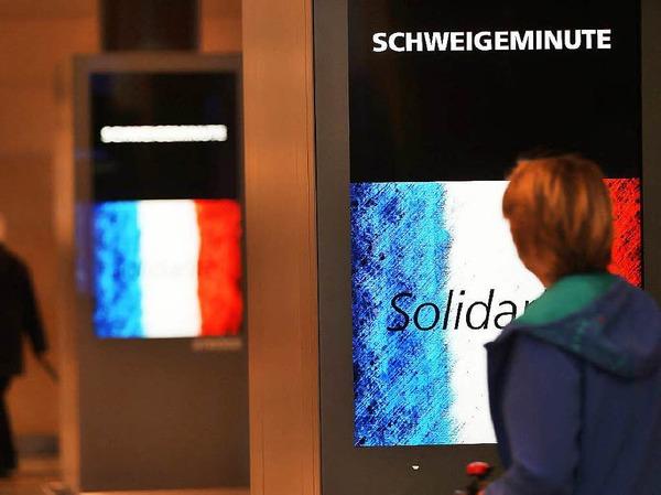Anzeigentafeln erinnern in Köln an die Schweigeminute für die Opfer von Paris.