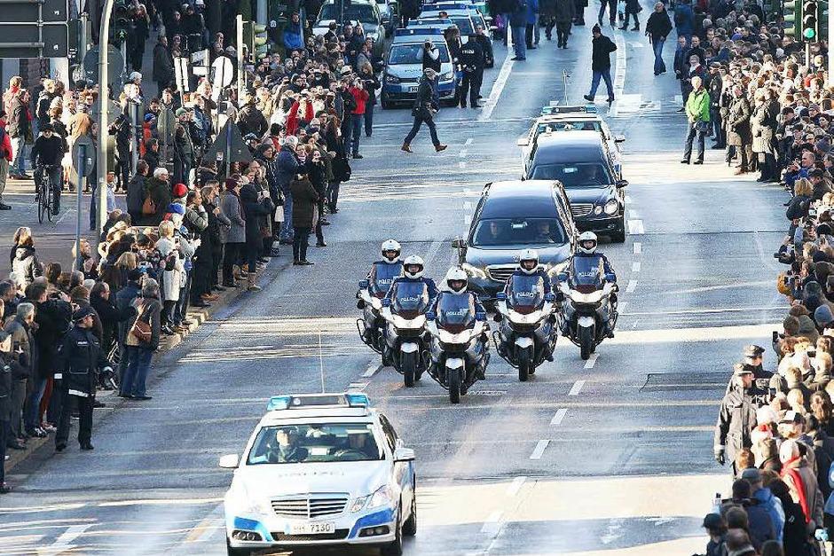 Eine Polizeieskorte führt den Trauerzug an. Tausende Menschen nehmen Abschied von Helmut Schmidt. (Foto: dpa)