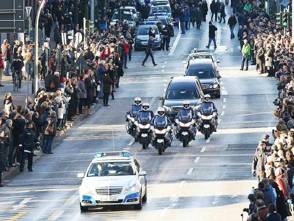 Eine Polizeieskorte führt den Trauerzug an. Tausende Menschen nehmen Abschied von Helmut Schmidt.