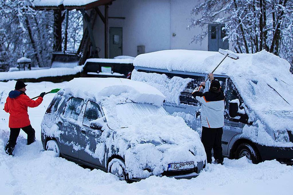 Autos werden in Oberwinden am Sonntag morgen vom Schnee befreit. (Foto: Daniel Fleig)