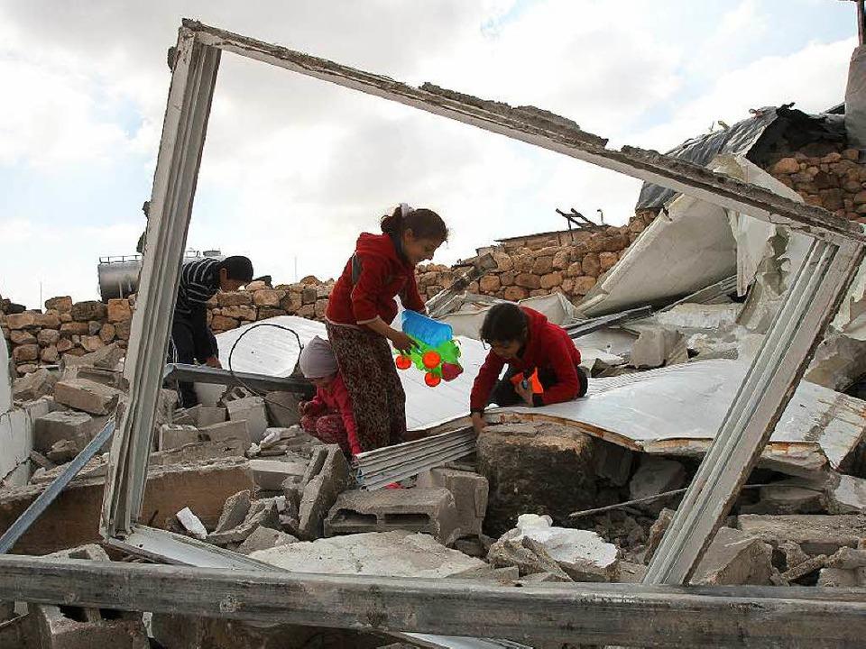 Palästinensische Kinder suchen in ihren abgerissenen Häusern nach Spielsachen.  | Foto: AFP