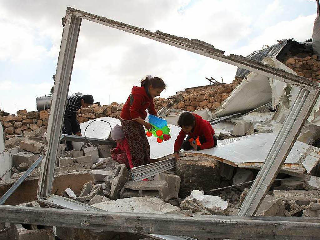 Palästinensische kinder suchen in ihren abgerissenen häusern
