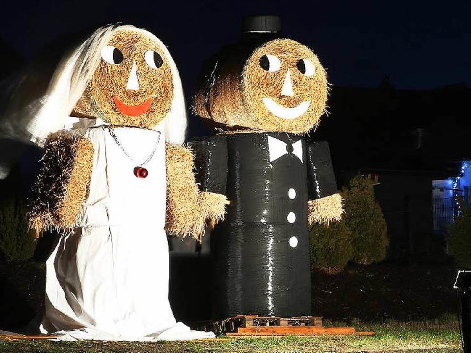 Ein aus Strohballen gebautes Hochzeitspaar   | Foto: dpa