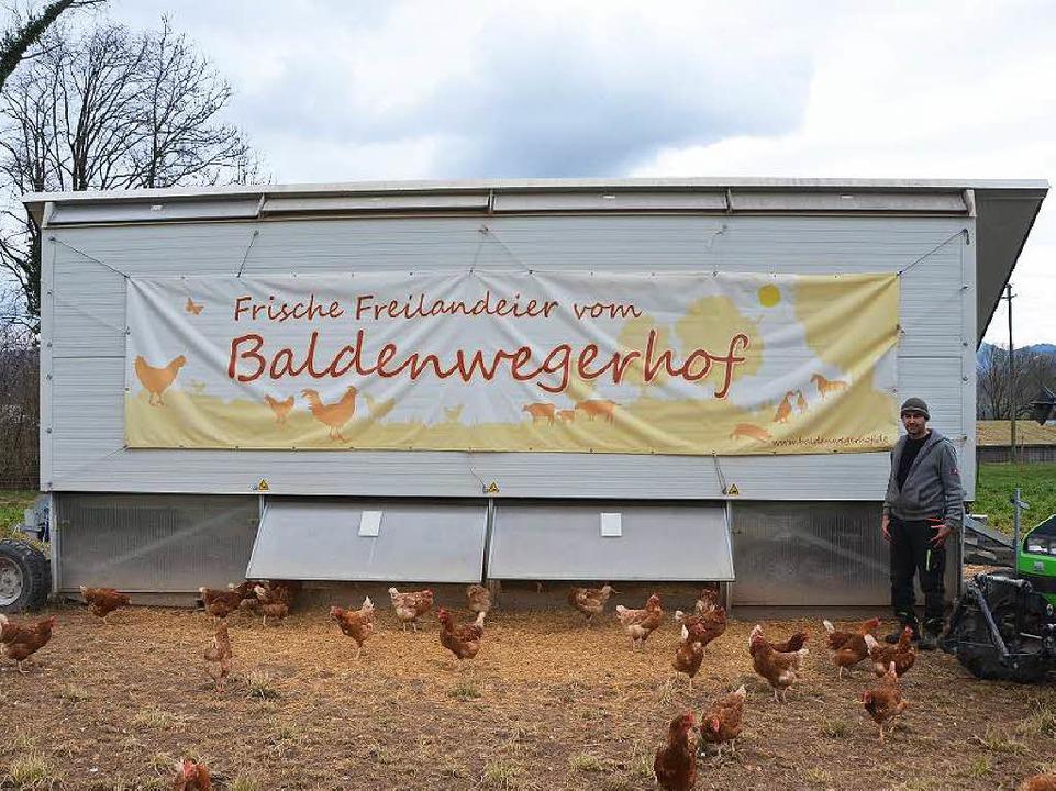Bernd Hug vor dem Hühnermobil und sein...ern auf dem Baldenweger Hof in Stegen.    Foto: Philip Müller