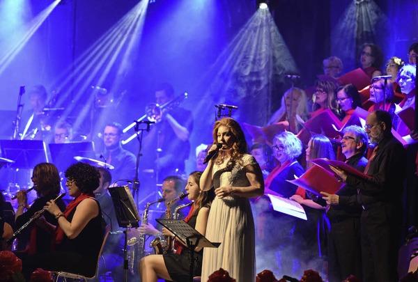 Sängerin Sarah Kettenmann umringt von Musikern und Chor auf der Bühne
