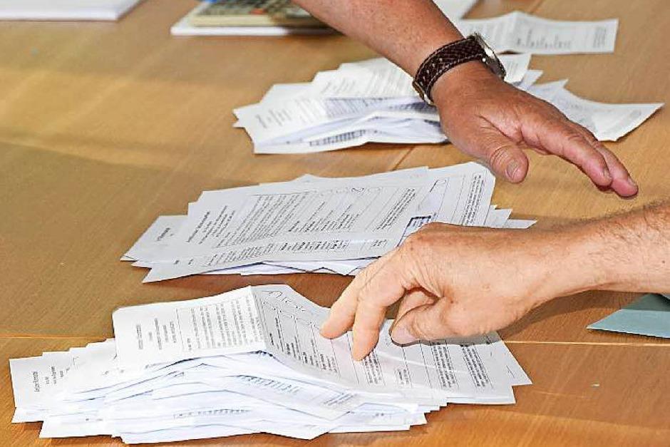 Die Stimmzettel stapeln sich, zahlreiche interessierte Bürger verfolgen die Auszählung im Bürgersaal des Rathauses. (Foto: Martin Wendel)