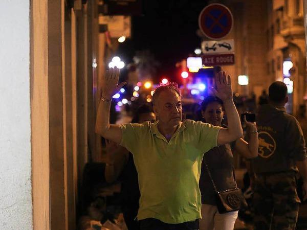 Menschen, die die Gefahrenzone verlassen, erheben die Hände, um zu zeigen, dass sie unbewaffnet sind.