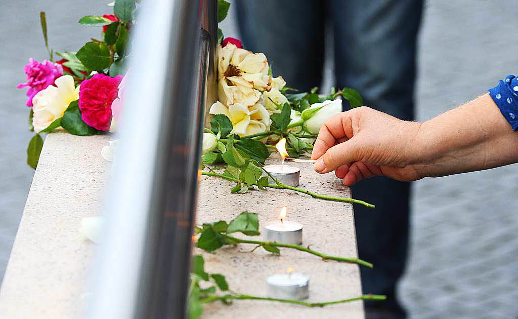 Nach der Bluttat von München zündet eine Frau beim Olympia Einkaufszentrum Kerzen