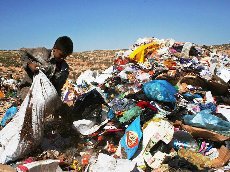 Im Westjordanland sucht ein Junge im Müll nach Brauchbarem.   | Foto: dpa