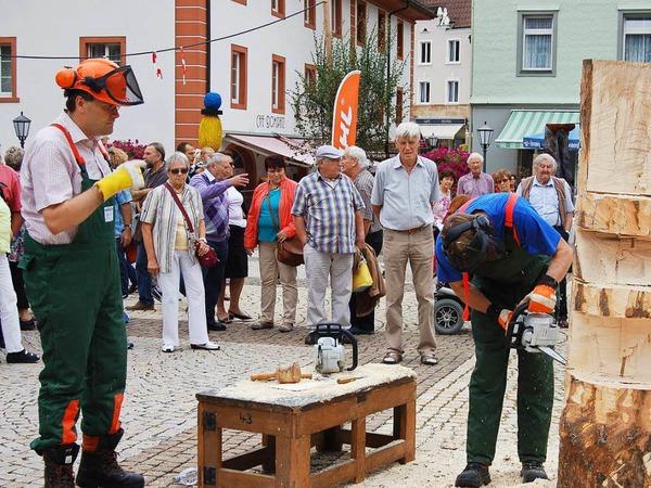 Landrat Martin Kistler (links) und St. Blasiens Bürgermeister Rainer Fritz gestalten am Abschlusstag gemeinsam eine Holzskulptur.