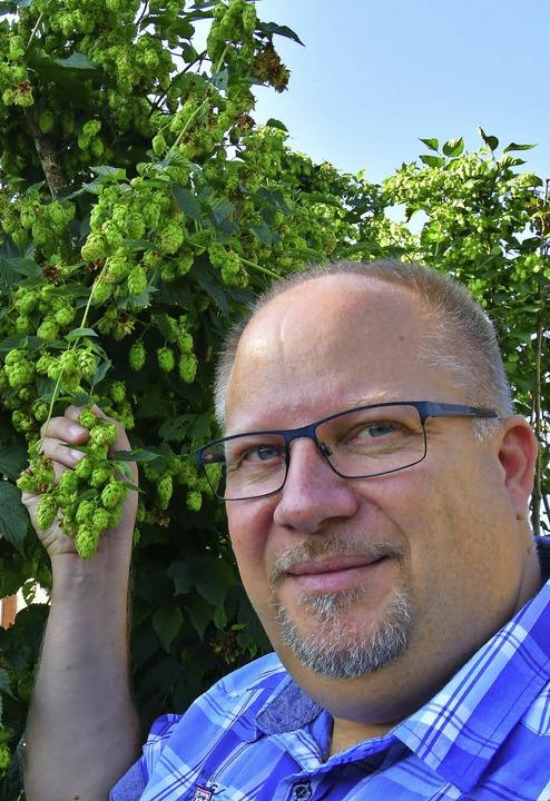Bierbrauer Matthias Seile mit einer Hopfenpflanze    Foto: Dieter Erggelet