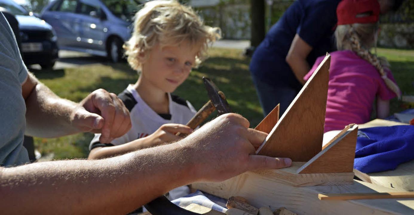 Der sechsjährige Thibault Muhlke baut ...r Jan ein Holzschiff für die Regatta.     Foto: Stella Kaltenbach