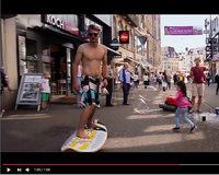 Typ ohne Hemd rollt mit Surfbrett durch Basler Innenstadt