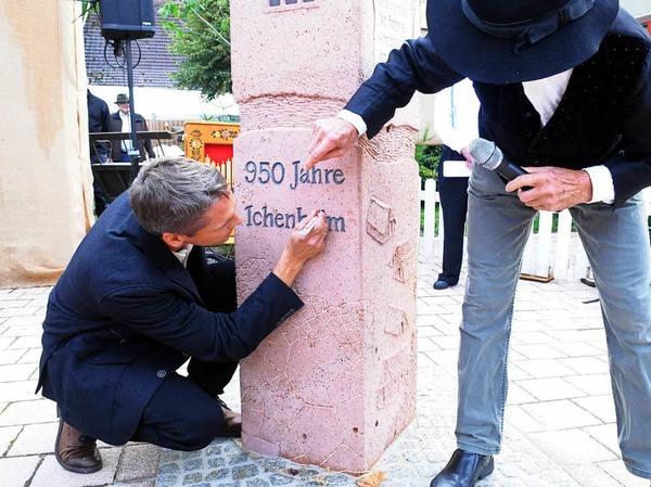 """Ortsvorsteher Ralf Wollenbär (links)  bringt das i-Tüpfelchen auf dem """"Ichenheim"""" an auf der Skulptur von Walter Henninger (rechts) an."""