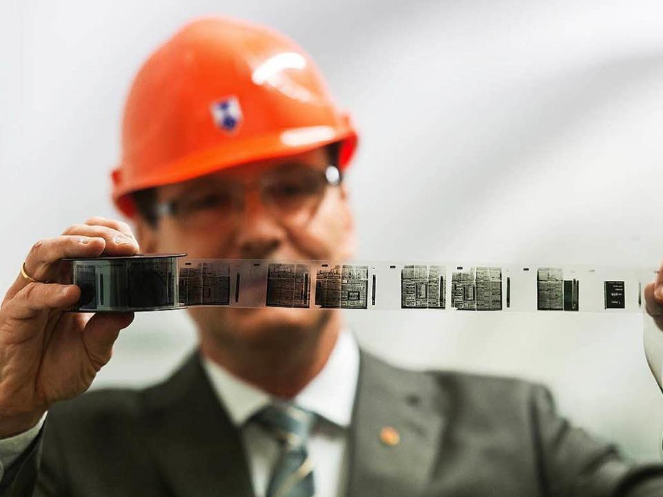 Christoph Unger, Präsident des Bundesa...phenhilfe, betrachtet einen Mikrofilm.    Foto: dpa
