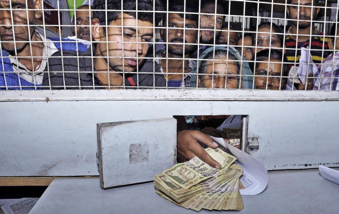 Menschen drängen sich im nordindischen...ültig gewordene  Scheine zu tauschen.   | Foto: dpa