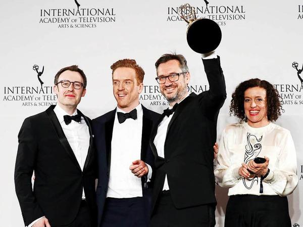 """Schauspielerin Maria Schrader und die Produzenten Philipp Steffens (links) und Jörg Winger (zweiter von rechts) posieren mit dem britischen Schauspieler Damian Lewis und dem Emmy für """"Deutschland 83""""."""