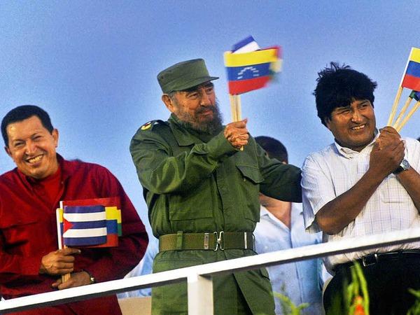 Der damalige venezolanische Präsident Hugo Chavez (l-r), der damalige kubanische Präsident Fidel Castro und Boliviens Präsident Evo Morales winken mit Fähnchen (undatierte Aufnahme).