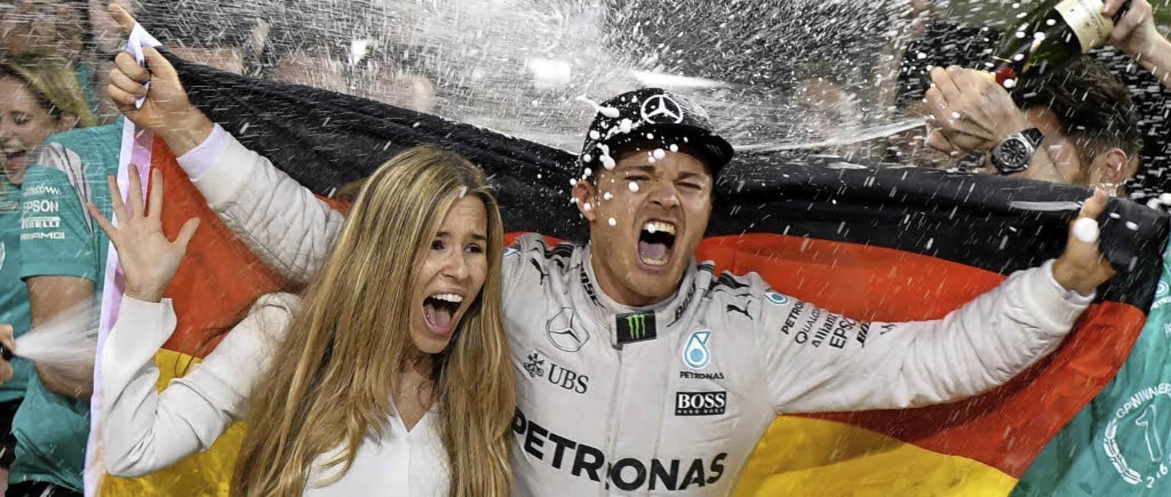 Champagnerdusche: Nico Rosberg und sei...ld werden vom Mercedes-Team gefeiert.     Foto: dpa