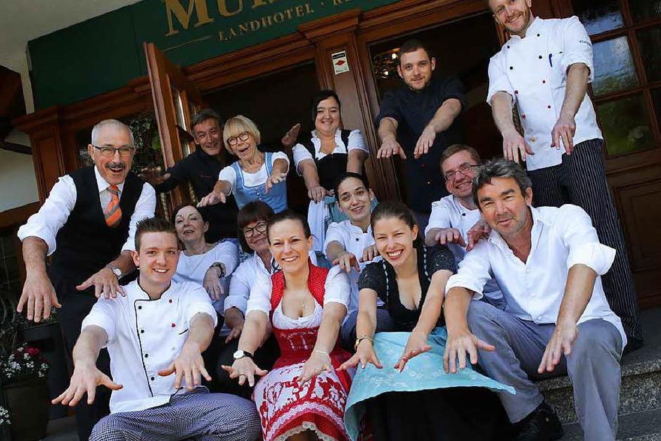 Küchenchef Stefan Rottler (vorne rechts) und Hotelchefin Anette Rottler (sechste von links, hockend in der mittleren Reihe) stimmen mit der Belegschaft zur 50-Jahr-Feier des Mühlenhofs eine La-Ola-Welle an. (Foto: Christoph Breithaupt)