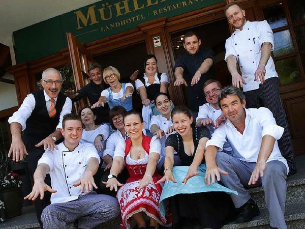 Küchenchef Stefan Rottler (vorne rechts) und Hotelchefin Anette Rottler (sechste von links, hockend in der mittleren Reihe) stimmen mit der Belegschaft zur 50-Jahr-Feier des Mühlenhofs eine La-Ola-Welle an.