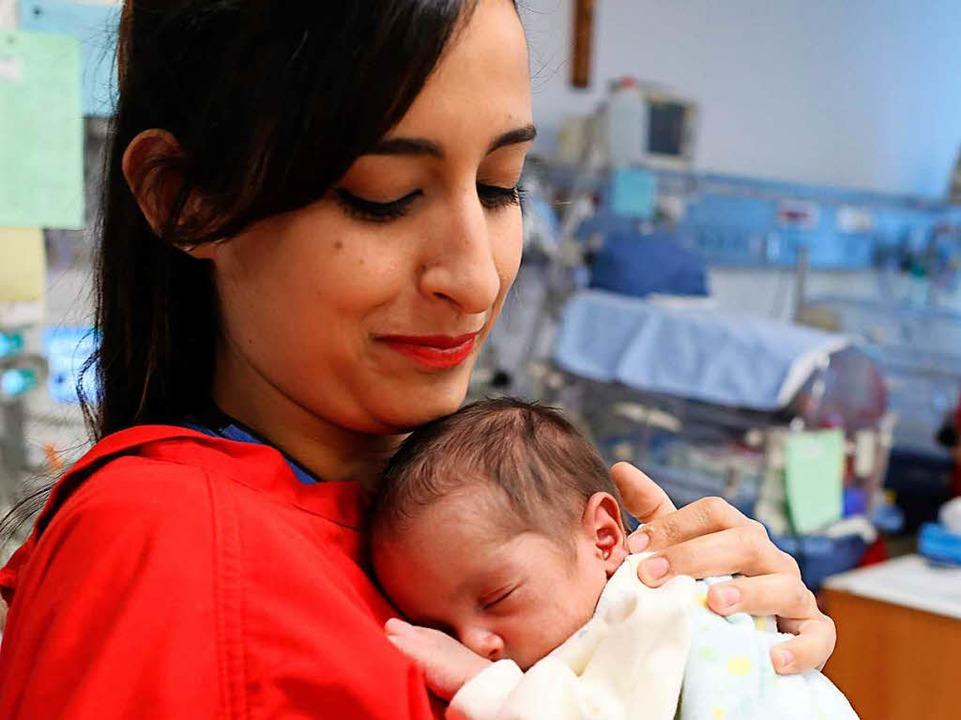 Auf der Frühchenstation der Klinik Zur...ter hält eines der Babys in den Armen.  | Foto: Sascha Montag/Zeitenspiegel