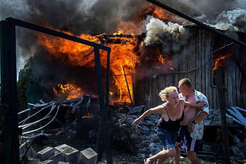 Menschen fliehen nach einem Luftangriff im Dorf Luhanskaya in der Ukraine. Das Foto von Valery Menikov erhielt den ersten Preis Long-Term Projects. (Foto: dpa)