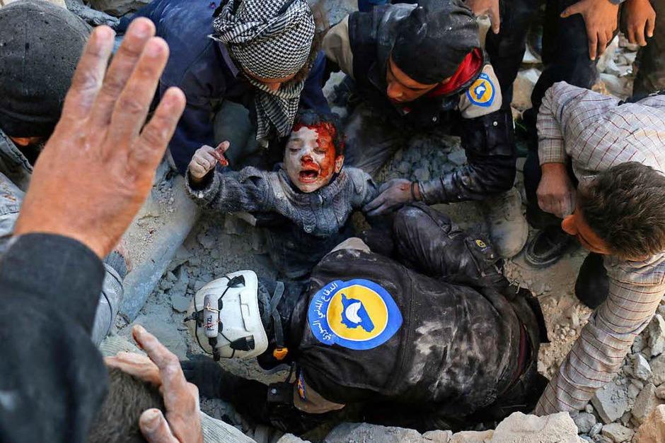 Syrische Zivilhelfer retten einen Jungen, der am 24. November 2016 in Aleppo (Syrien) aus einem nach einem Angriff mit einer Fassbombe (laut Berichten) zusammengestürzten Haus gerettet wird.  Das Bild von Ameer Alhalbi (AFP) wird mit dem zweiten Preis in der Kategorie Spot News, Einzelbild, ausgezeichnet. (Foto: dpa)