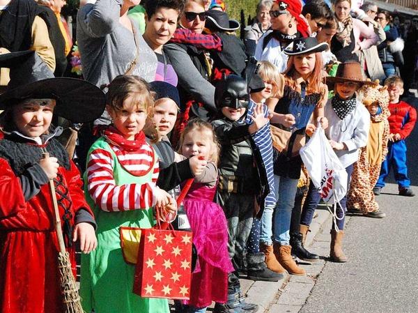 Viele kleine Narren warten am Straßenrand auf die großen und auf Süßigkeiten.