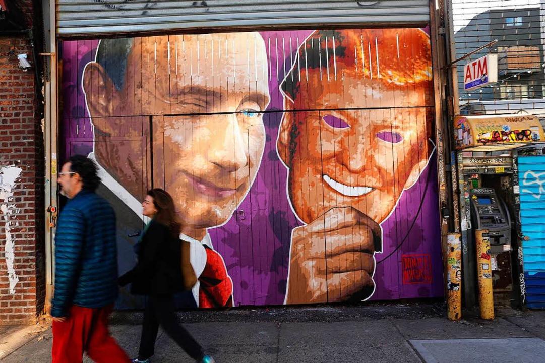 Straßenkunst in New York: Putin mit einer Trump-Maske in der Hand.    | Foto: AFP
