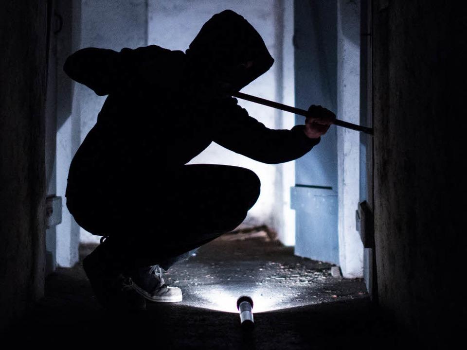 Ein fiktiver Einbrecher hebelt eine Tür auf (Symbolbild).    Foto: dpa