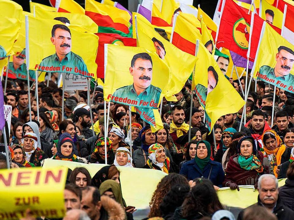 Teilnehmer der Kundgebung in Frankfurt... Bildern von PKK-Chef Öcalan mit sich.  | Foto: dpa