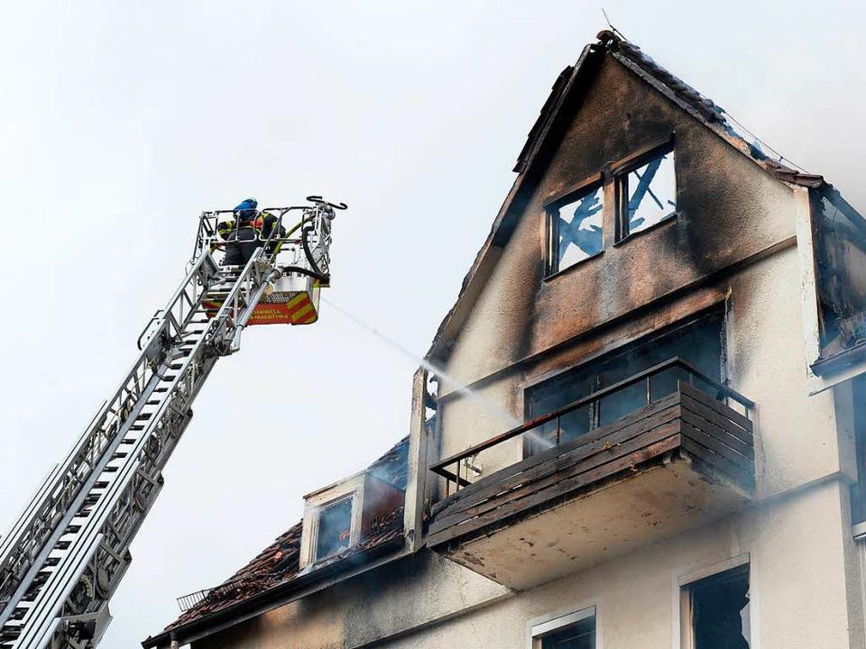 Feuerwehrleute auf einer Drehleiter lö...wohner des Hauses tödlich verunglückt.  | Foto: dpa