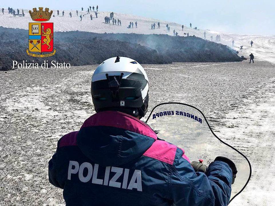 Ein Polizist kommt auf dem Schneemobil Touristen zu Hilfe.    | Foto: dpa