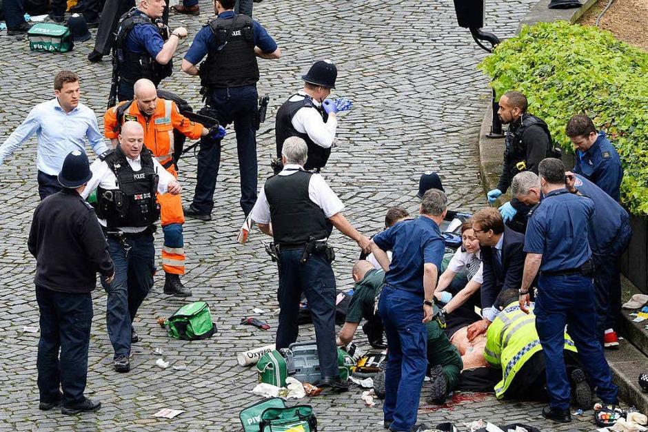 Parlamentsabgeordneter Tobias Ellwood (Mitte) kümmert sich um verletzte Personen. (Foto: dpa)