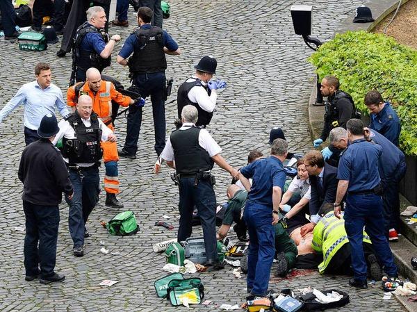 Parlamentsabgeordneter Tobias Ellwood (Mitte) kümmert sich um verletzte Personen.