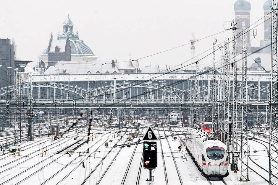 Verschneite Gleisanlagen sind am Dienstag vor dem Hauptbahnhof in München, im Hintergrund die Frauenkirche. (Foto: dpa)