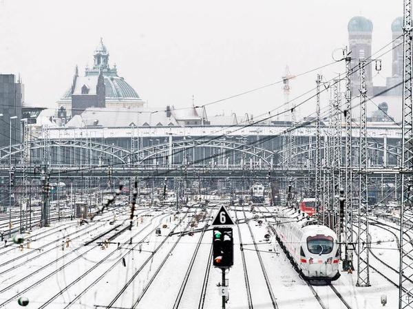 Verschneite Gleisanlagen sind am Dienstag vor dem Hauptbahnhof in München, im Hintergrund die Frauenkirche.