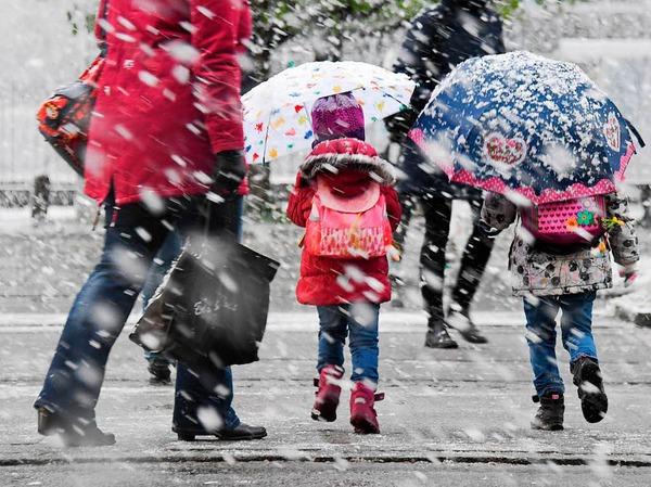 Zwei Kinder mit Regenschirmen gehen am Dienstag in München  bei Schneefall über eine Straße.