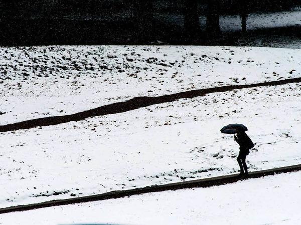 Eine Frau läuft am Ostermontag auf dem Feldberg im Schwarzwald  mit dem Regenschirm an verschneiten Wiesen vorbei.