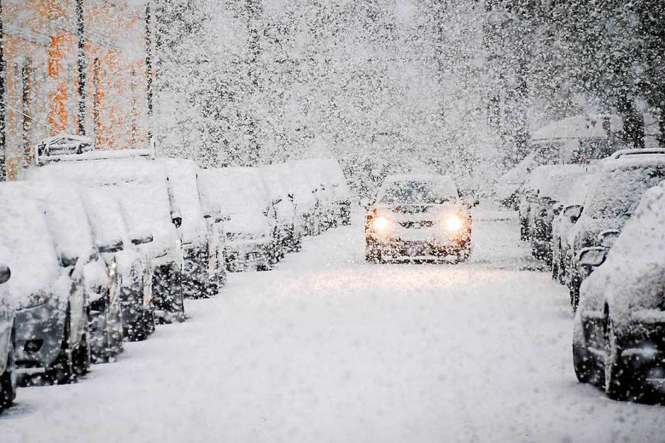 Ein Auto fährt am Dienstag durch einen verschneite Straße in München. (Foto: dpa)